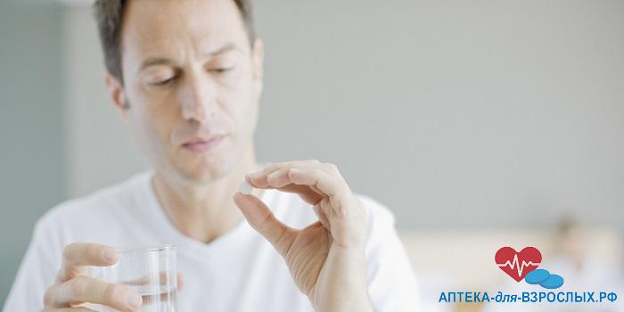 Мужчина держит таблетку в руке
