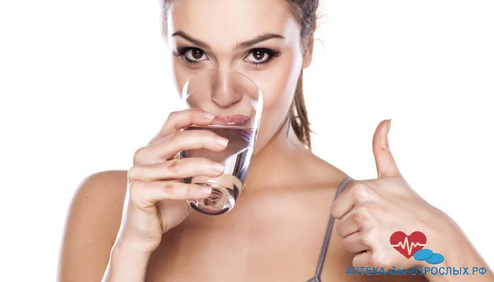 Брюнетка пьет воду и показывает большой палец вверх