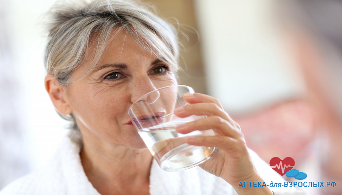 Женщина в возрасте держит стакан воды