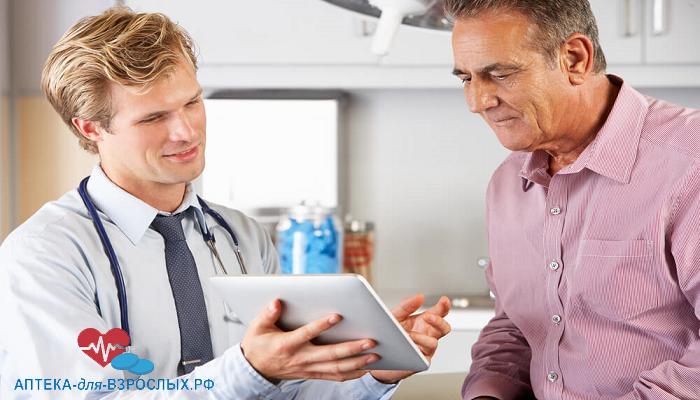 Молодой врач показывает пациенту информацию на планшете