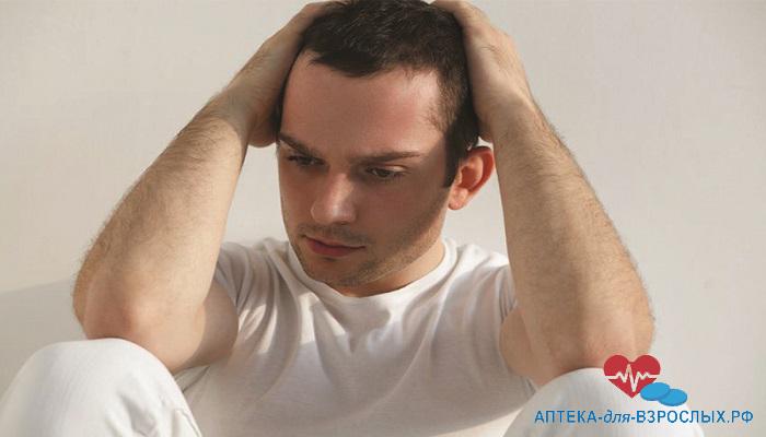 Мужчина держится руками за голову из-за побочных реакций от добавки