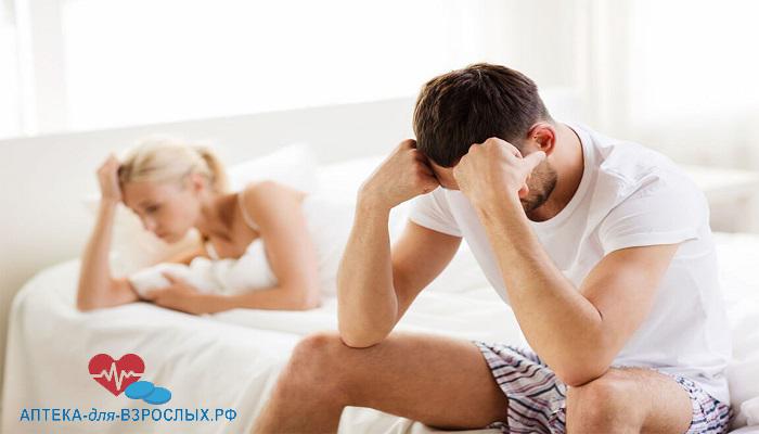 Мужчина и девушка сидят на кровати и держатся за головы