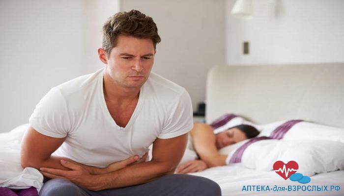 Мужчина сидит на кровати и держится за живот