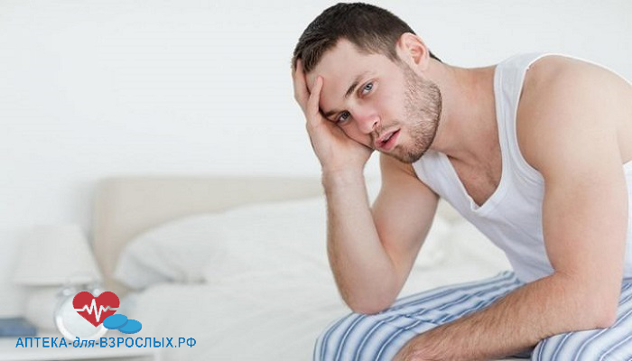 Мужчина сидит на кровати и держится рукой за голову из-за неправильного использования добавки