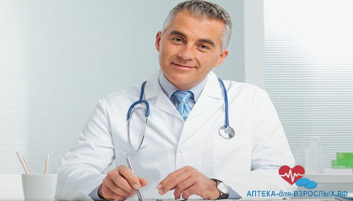 Седоволосый врач сидит за столом