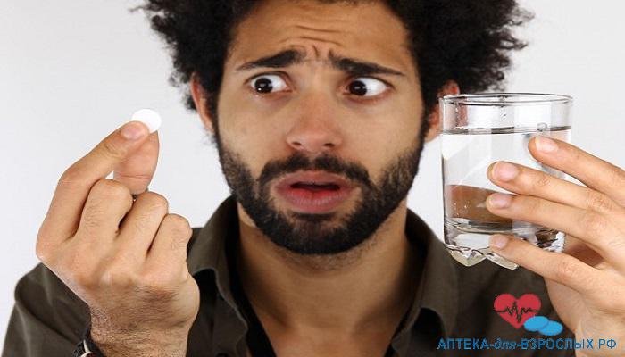 Смуглый мужчина удивленно смотрит на таблетку от импотенции Эромакс